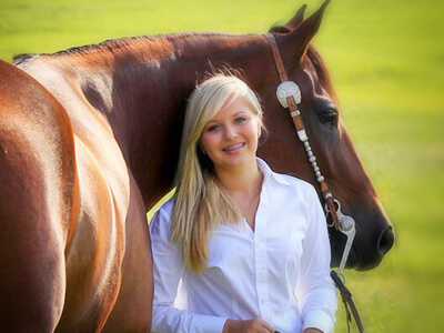 girl standing in front of shiny horse