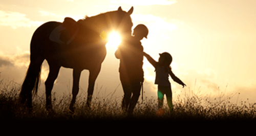Mother and daughter with horse standing in a field at sunset.